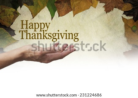 Happy Thanksgiving Parchment Autumn Leaves banner - Woman's outstretched hand with palm up and a 'Happy Thanksgiving' floating above on a parchment background edged with autumn leaves fading to white - stock photo