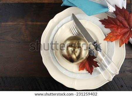 Happy Thanksgiving table place setting in pale aqua blue and white theme with gold fruit and candle on dark wood background. - stock photo