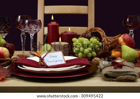 Happy Thanksgiving table setting in classic rustic colors on wood table with cornucopia centerpiece, candles and fruit.  - stock photo
