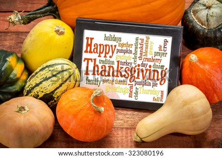 Happy Thanksgiving word cloud on a digital tablet surrounded by pumpkin and winter squash - stock photo