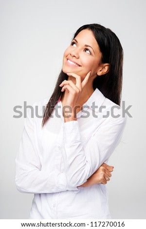 happy thinking woman looking up with hand on chin and copyspace isolated on grey - stock photo