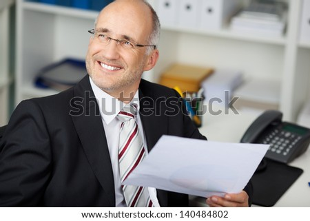 Happy thoughtful businessman holding paper while looking away at office desk - stock photo