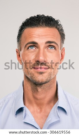 Happy thoughtful man looking up over gray background - stock photo