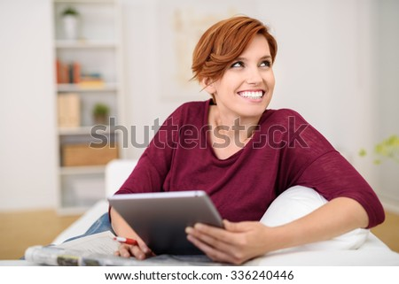 Happy Thoughtful Young Woman Answering Crossword Puzzle on Newspaper using Tablet Computer at the Living Room. - stock photo