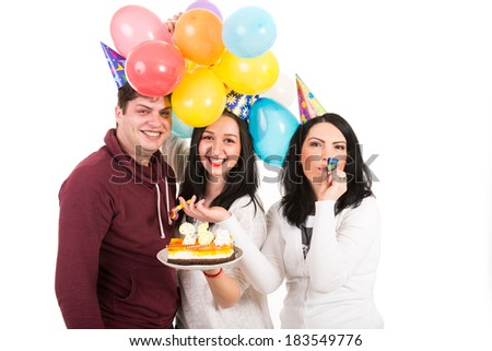 Happy three friends at woman birthday with cake and balloons blow out horn party isolated on white background - stock photo