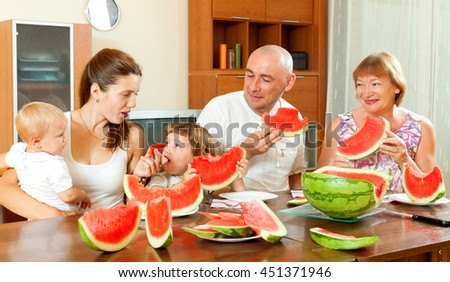 Happy three generations family eating watermelon  over  table at home interior
