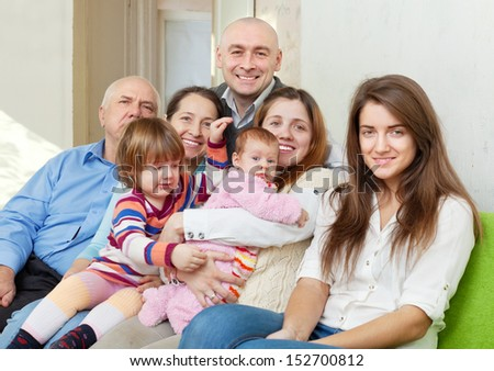 Happy three generations family sits on sofa in livingroom  - stock photo