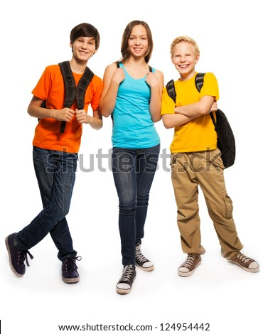 Happy three teen kids with backpacks standing isolated on white - stock photo