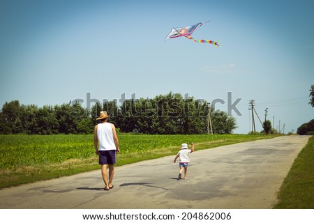 happy times: image of father & son having fun playing with kite outdoors on summer sunny day green woods & blue sky outdoors copy space background - stock photo