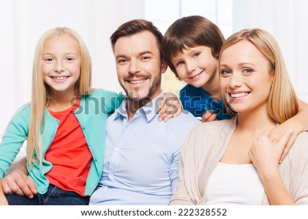 Happy to be a family. Happy family of four bonding to each other and smiling while sitting indoors  - stock photo