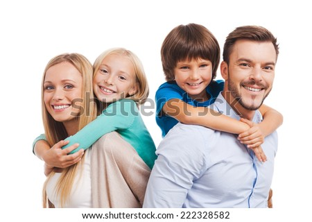 Happy to be a family. Happy family of four bonding to each other and smiling while standing against white background  - stock photo