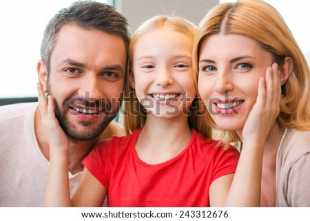 Happy to be a family. Happy family of three bonding to each other and smiling while sitting indoors  - stock photo
