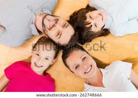 Happy to be a family. Top view of happy family of four bonding to each other heads and smiling while lying on the h floor - stock photo