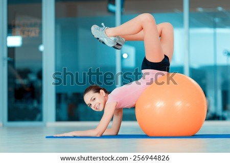 Happy to be fit. Portrait of attractive teenage girl lying on fitness ball and smiling at camera while training in sports club - stock photo
