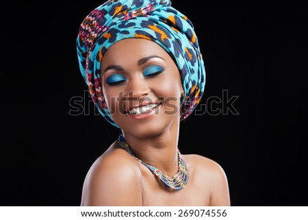 Happy to be herself. Happy young African woman wearing a headscarf and necklace and keeping eyes closed while standing against black background - stock photo