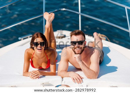 Happy to be on vacation. Cheerful young couple sunbathing while lying on the deck of yacht  - stock photo