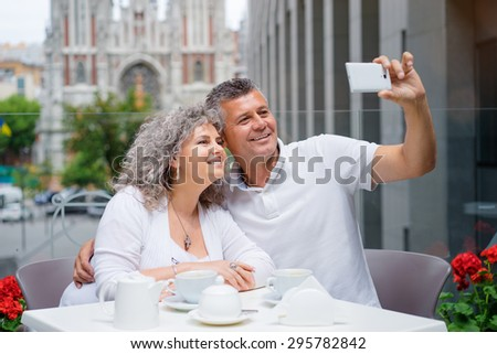 Happy to be together. Attractive elderly family couple taking selfie on smartphone in side walk cafe. - stock photo