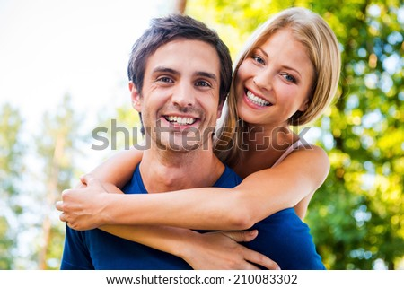 Happy to be together. Low angle view of beautiful young loving couple standing outdoors together while woman hugging her boyfriend and smiling - stock photo