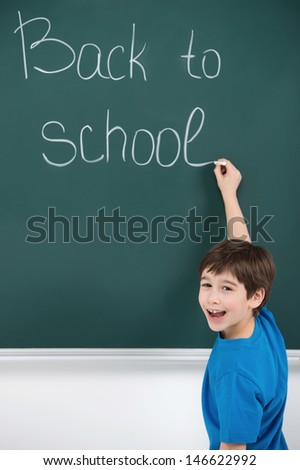Happy to come back. Cheerful little schoolboy writing on the blackboard - stock photo