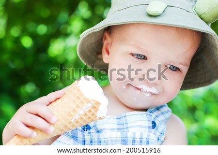 happy toddler boy eating ice cream on a summer day - stock photo