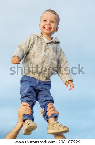 Happy Toddler boy in his father's arms - stock photo