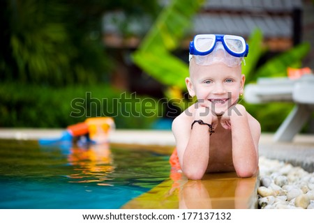 Happy toddler boy in swimming pool wearing mask outdoors - stock photo