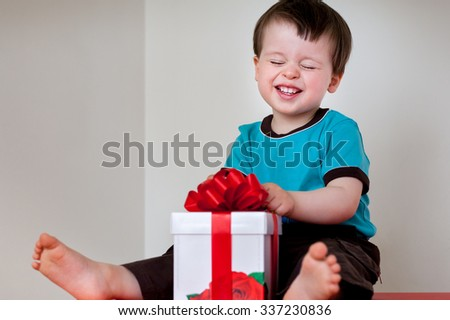Happy toddler boy opening gift box indoors - stock photo