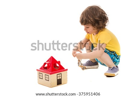 Happy toddler boy opening toy house isolated on white background