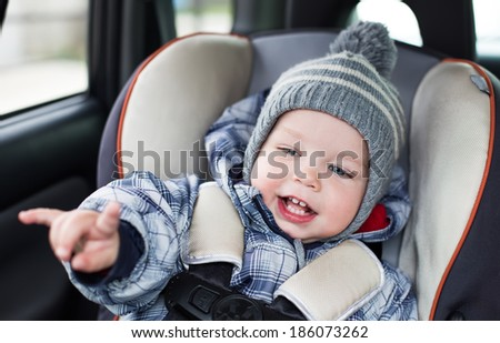 happy toddler  boy sitting in the car seat and shows a rock gesture - stock photo