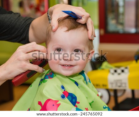 Happy toddler child getting his first haircut