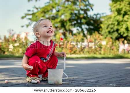 happy toddler draws with chalk on asphalt - stock photo