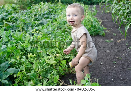 Happy Toddler exploring a garden and getting dirty - stock photo