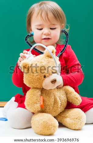 Happy toddler girl caring for her teddy bear with a stethoscope  - stock photo