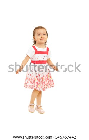 Happy toddler girl in beautiful dress posing isolated on white background