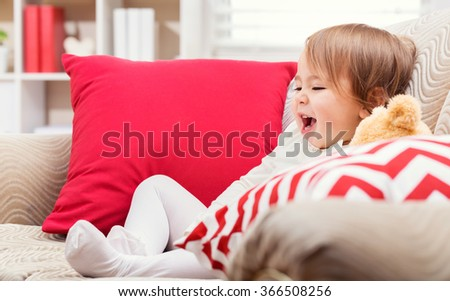 Happy toddler girl laughing in her living room - stock photo