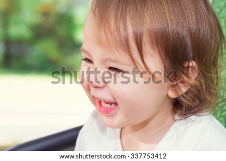 Happy toddler girl laughing while playing on a swing outside - stock photo