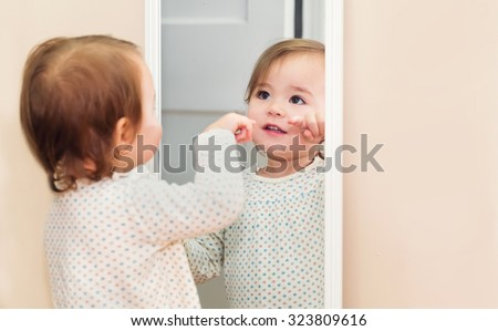 Happy toddler girl looking at herself in the mirror in her house - stock photo