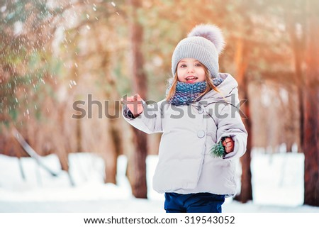 happy toddler girl on the walk in snowy winter forest - stock photo
