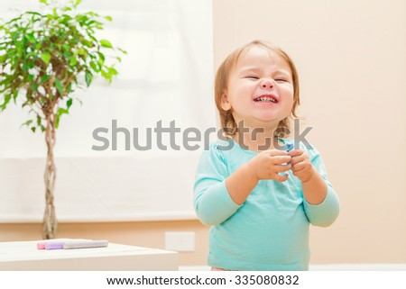 Happy toddler girl playing with chalk inside her house