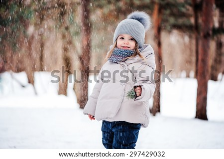 happy toddler girl playing with snow in winter park - stock photo