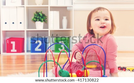 Happy toddler girl playing with toys in her house - stock photo