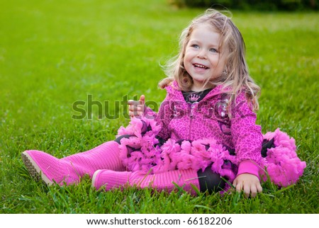 Happy toddler girl sitting on green grass - stock photo