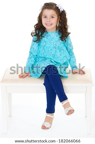 happy toddler girl sitting on the bench.Isolated on white background. - stock photo