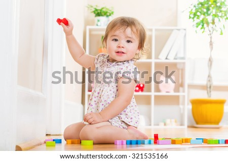 Happy toddler girl smiling and playing with her toy blocks inside her house
