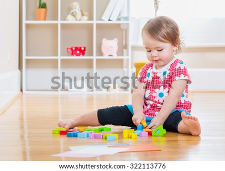 Happy toddler girl smiling and playing with wooden toy blocks inside her house - stock photo