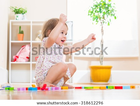 Happy toddler girl smiling while playing with her wooden toy blocks  - stock photo