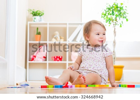 Happy toddler girl smiling while playing with toy blocks  - stock photo