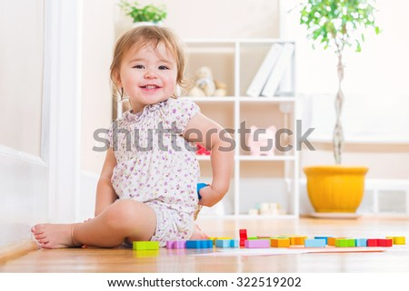 Happy toddler girl smiling while playing with wooden toy blocks inside her house - stock photo