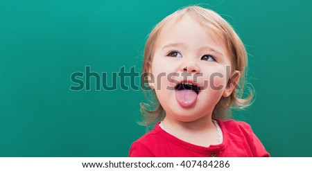 Happy toddler girl sticking her tongue out in front of a green chalkboard - stock photo