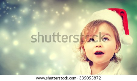 Happy Toddler girl with a Santa hat  - stock photo